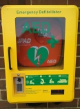 Wall mounted defibrillator in bright yellow wall box